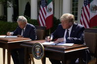 President Donald Trump and Mexican President Andres Manuel Lopez Obrador sign a joint declaration at the White House, Wednesday, July 8, 2020, in Washington. (AP Photo/Evan Vucci)