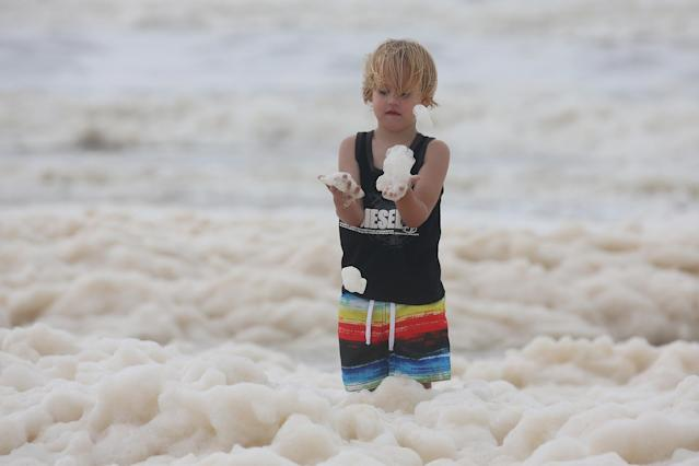 A child plays with ocean foam in Burleigh Heads as Queensland experiences severe rains and flooding from Tropical Cyclone Oswald on January 28, 2013 in Gold Coast, Australia. Hundreds have been evacuated from the towns of Gladstone and Bunderberg while the rest of Queensland braces for more flooding. (Photo by Chris Hyde/Getty Images)