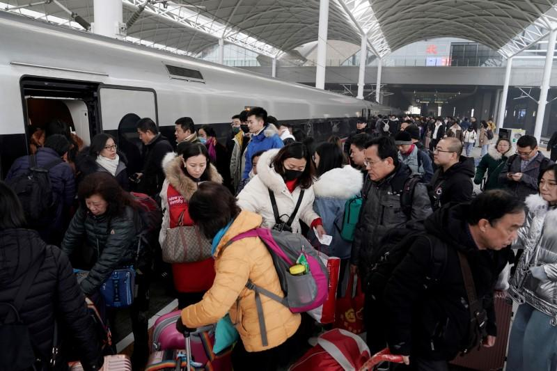 FILE PHOTO: File picture of travellers boarding a train at a railway station in China as the annual Spring Festival travel rush begins ahead of the Chinese Lunar New Year