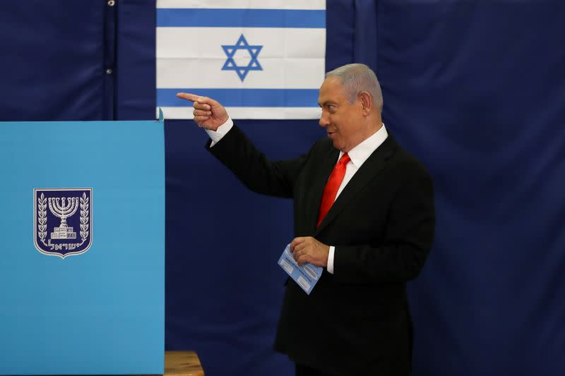 FILE PHOTO: Israeli Prime Minister Benjamin Netanyahu gestures while standing near a voting booth as he prepares to cast his ballot in Israel's general election, at a polling station in Jerusalem