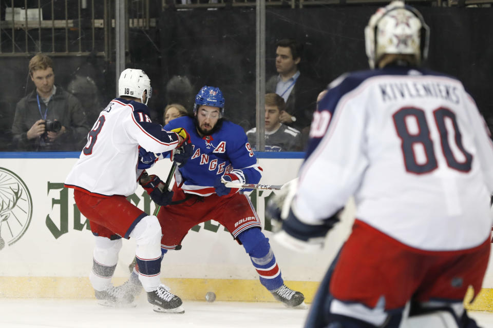 Columbus Blue Jackets center Pierre-Luc Dubois (18) defends New York Rangers center Mika Zibanejad (93) as Columbus Blue Jackets goaltender Matiss Kivlenieks (80) looks on during the second period of an NHL hockey game, Sunday, Jan. 19, 2020, in New York. (AP Photo/Kathy Willens)