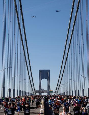Athletics - New York City Marathon - New York City, New York, U.S. - November 4, 2018 Runners cross the Verrazzano Bridge during the marathon as helicopters pass overhead REUTERS/Andrew Kelly