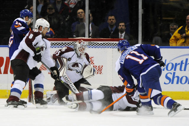 Colorado Avalanche goalie Jean-Sebastien Giguere (35) stops a shot on goal by New York Islanders' Lubomir Visnovsky (11) as Colorado Avalanche's Jan Hejda (8) defends against Islanders' Josh Bailey (12) in the third period of an NHL hockey game on Saturday, Feb. 8, 2014, in Uniondale, N.Y. The Avalanche won 4-2. (AP Photo/Kathy Kmonicek)