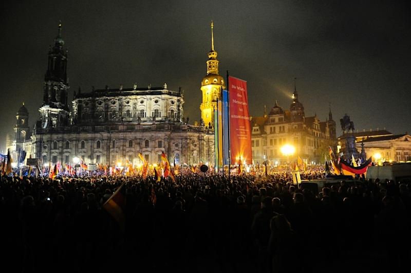 "Supporters of the PEGIDA movement, which translates to ""Patriotic Europeans Against the Islamisation of the Occident"" gather at a protest rally on October 19, 2015 in Dresden, Germany (AFP Photo/Robert Michael)"