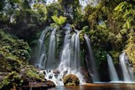 """<p><strong>Where and what is this?</strong><br> Banyu Wana Amertha Waterfall, a recently opened Northern Bali attraction, is a little hard to get to. You'll need to drive at least 90 minutes from <a href=""""https://www.cntraveler.com/story/finding-the-bali-you-came-for?mbid=synd_yahoo_rss"""" rel=""""nofollow noopener"""" target=""""_blank"""" data-ylk=""""slk:Ubud"""" class=""""link rapid-noclick-resp"""">Ubud</a> and take a winding, 20-minute hike through a banana plantation. But once you've completed the journey, you'll be rewarded handsomely with a lush forest hiding a set of grand waterfalls that are somehow not overrun by crowds.</p> <p><strong>So what can we expect to experience?</strong><br> You're here for the falls and, depending on the season, you might be able to safely access all four. The main waterfall is the most spectacular—a verdant rock amphitheater with misty streams cascading down to a shallow pool. Come at an opportune time of the day—the earlier the better—and you might have this slice of paradise all to yourself.</p> <p><strong>Is it easy to get around?</strong><br> Clearly marked signage, natural paths and steps, wooden bridges, and helpful locals makes access a breeze, but this isn't suitable for anyone with mobility issues.</p> <p><strong>Why this, out of all the sites in Bali?</strong><br> In Bali, it's rare to find a splendid attraction unsullied by the traveling masses—go before word catches on.</p>"""