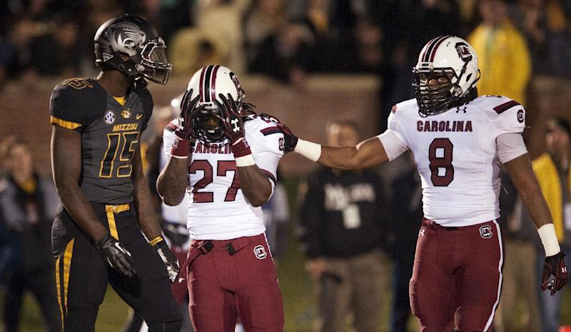 South Carolina's Kaiwan Lewis, right, consoles teammate Victor Hampton, center, as Missouri wide receiver Dorial Green-Beckham, left, walks by after Hampton nearly had an interception during the third quarter of an NCAA college football game Saturday, Oct. 26, 2013, in Columbia, Mo. (AP Photo/L.G. Patterson)