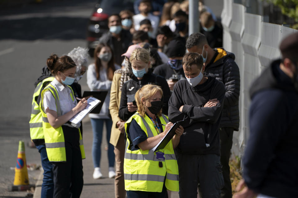 FILE - In this May 18, 2021, file photo, people queue for vaccinations against coronavirus at the ESSA academy in Bolton, England. Coronavirus infections, hospitalizations and deaths are plummeting across much of Europe. Vaccination rates are accelerating, and with them, the promise of summer vacations. (AP Photo/Jon Super, File)