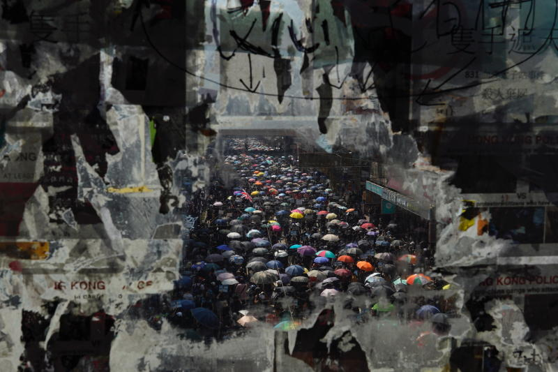 Marching anti-government protesters are seen through a glass with peeled off posters, Tuesday, Oct. 1, 2019, in Hong Kong while the celebration of the People's Republic's 70th anniversary is taking place in Beijing. (Photo: Vincent Yu/AP)