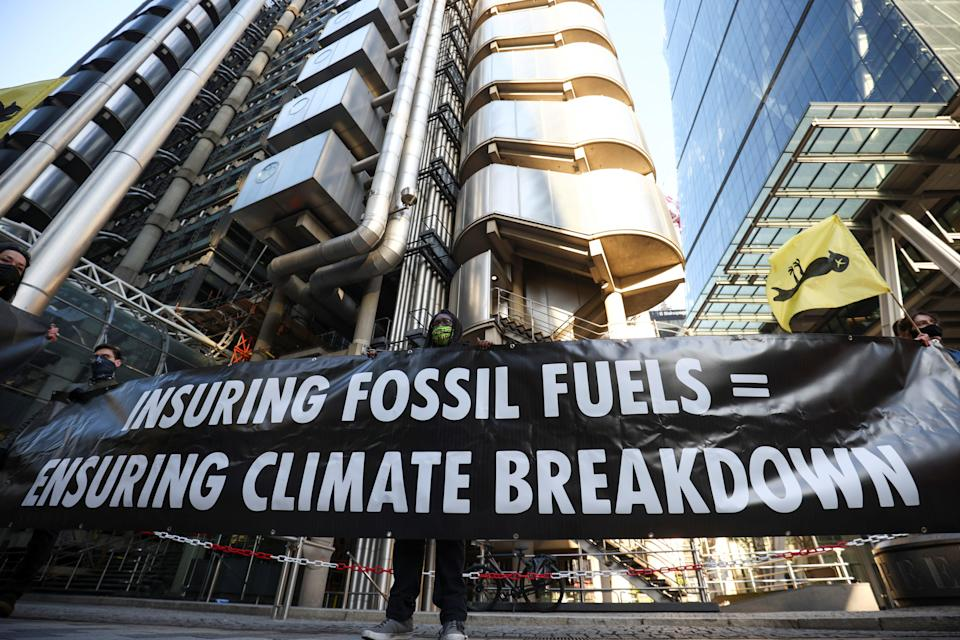 Activists from Extinction Rebellion, a global environmental movement, hold a banner as they protest outside the Lloyd's building in London.REUTERS