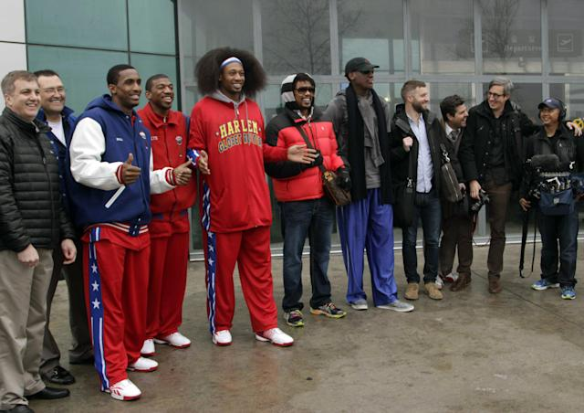 "Flamboyant former NBA star Dennis Rodman, fifth from right, poses with three members of the Harlem Globetrotters basketball team, in red jerseys, and a production crew for the media upon arrival at Pyongyang Airport, North Korea, Tuesday, Feb. 26, 2013. Rodman known as ""The Worm"" arrived in Pyongyang, becoming an unlikely ambassador for sports diplomacy at a time of heightened tensions between the U.S. and North Korea. (AP Photo/Kim Kwang Hyon)"