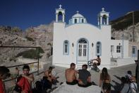 Children gather in front of a Greek Orthodox church on the Aegean Sea island of Milos, Greece, on Sunday, May 24, 2020. Greece's long-awaited tourist season will begin on June 15 with the opening of seasonal hotels and the arrival of the first foreign visitors, while international flights will begin heading directly for holiday destinations gradually as of July 1. (AP Photo/Thanassis Stavrakis)
