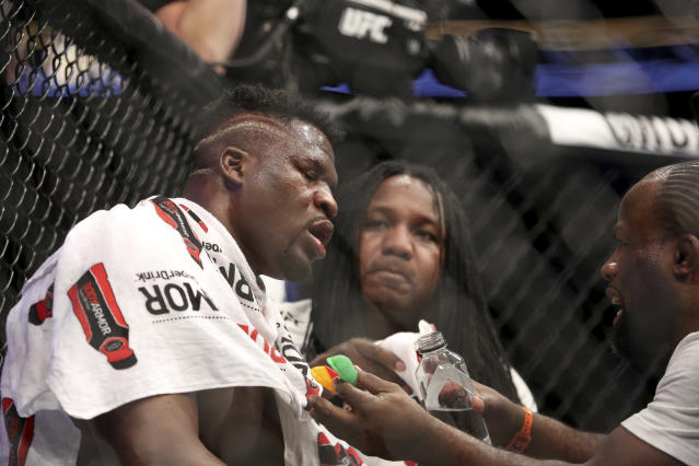 An exhausted Francis Ngannou sits seen in his corner before the fifth round against Stipe Miocic during a heavyweight championship mixed martial arts bout at UFC 220, early Sunday, Jan. 21, 2018, in Boston. Miocic retained his title via unanimous decision. (AP Photo/Gregory Payan)