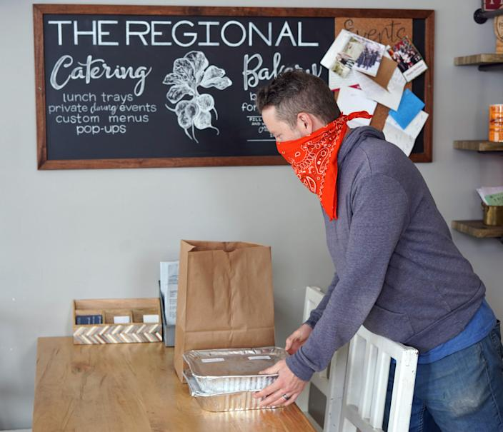 Kevin Grossi, the owner of the Fort Collins, Colorado-based restaurant The Regional, stacks to-go orders on a table ready for pickup during the coronavirus outbreak. Grossi is struggling to keep his 18-month-old restaurant running during the widespread closure orders.