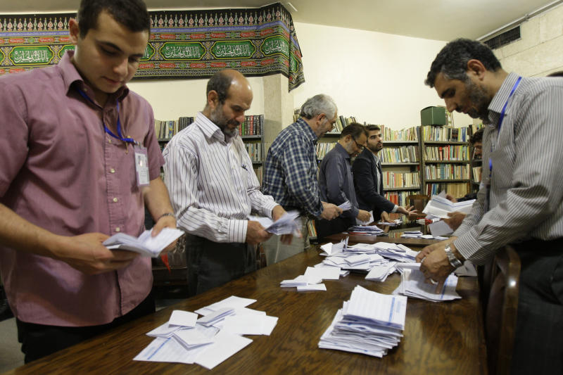 Iranian electoral workers count ballots in a polling station in Tehran, Iran, Friday, May 4, 2012. 130 hopefuls competed for 65 seats in 33 constituencies including the capital Tehran with 25 undecided seats. Conservative opponents of President Mahmoud Ahmadinejad have already won majority of seats of the new parliament in the first round of the elections in March. (AP Photo/Vahid Salemi)