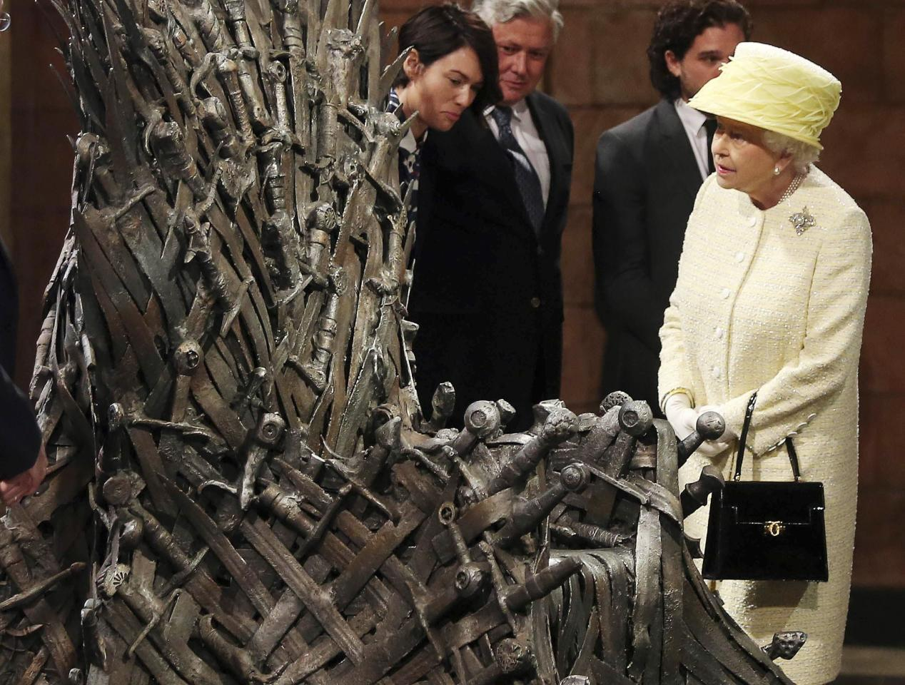 Britain's Queen Elizabeth looks at the Iron Throne next to Game of Thrones cast members Kit Harington (2nd R), Conleth Hill (2nd L) and Lena Headey (L), on the set of the television series in the Titanic Quarter of Belfast, Northern Ireland, June 24, 2014. REUTERS/Jonathan Porter/Pool (NORTHERN IRELAND - Tags: ROYALS ENTERTAINMENT SOCIETY TPX IMAGES OF THE DAY)