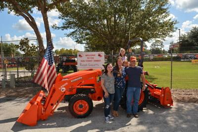 Marine Corps veteran Russell Guzzetta, who owns and operates Country Song Farm in Lithia, Florida, stands with his family in front of the Kubota L Series compact tractor he was awarded through Kubota's Geared to Give program during a special ceremony October 3.