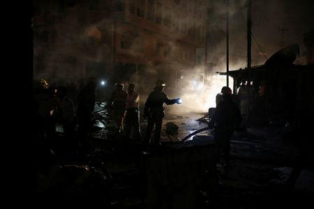 Members of Iraqi security forces inspect the site of car bomb attack in Baghdad