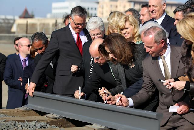 Gov. Jerry Brown, center left, and his wife Anne Gust, fourth from right, sign a portion of the rail at the California High Speed Rail Authority ground breaking event as Gina McCarthy, administrator of the U.S. Environmental Protection Agency, standing next to Brown at left, watches, Tuesday, Jan. 6, 2015 in Fresno, Calif. Gina McCarthy. California's high-speed rail project has become the first in the nation to break ground. Tuesday's groundbreaking was attended by several hundred people who gathered near old rail lines in an industrial section of downtown Fresno. (AP Photo/Gary Kazanjian)