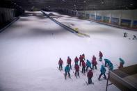 People warm up inside an indoor ski park at Qiaobo Ice and Snow World in Shaoxing