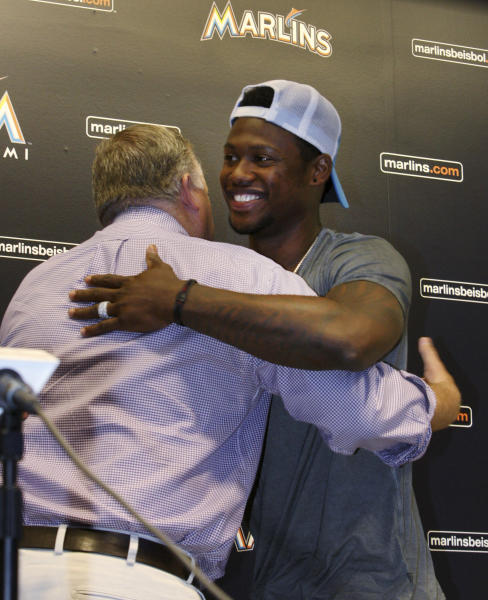 Former Miami Marlins third baseman Hanley Ramirez, right, hugs Marlins' president of baseball operations Larry Beinfest, after a news conference where Ramirez spoke about his trade, Wednesday July 25, 2012 in Miami. The Los Angeles Dodgers have worked out a multiplayer trade to acquire the former NL batting champion from Miami, the second big deal in as many days for the disappointing Marlins. (AP Photo/Wilfredo Lee)