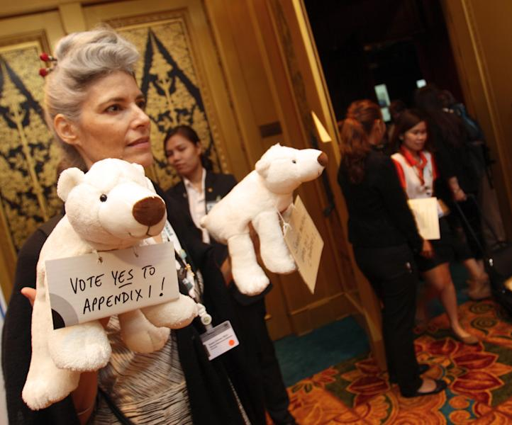 A representative from a wildlife organization hands out stuffed polar bear dolls to delegates before they vote on a proposal by Washington to change the status of the polar bear from a species whose trade is merely regulated, not banned at the Convention on International Trade in Endangered Species, in Bangkok, Thailand Thursday, March 7, 2013. The proposal by the United States to ban cross-border trade in polar bears and their parts was defeated Thursday at an international meeting of conservationists, marking a victory for Canada's indigenous Inuit people over their big neighbor to the south. (AP Photo/Sakchai Lalit)