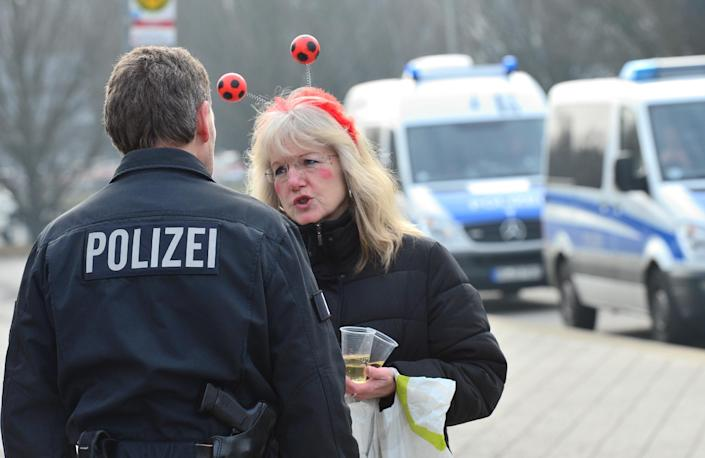 A police officer speaks with a women dressed up ready for the carnival in Braunschweig (AFP Photo/Julian Stratenschulte)