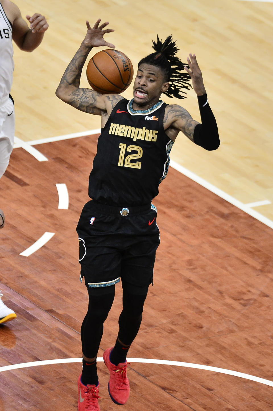 Memphis Grizzlies guard Ja Morant (12) scores against the San Antonio Spurs during the second half of an NBA basketball Western Conference play-in game Wednesday, May 19, 2021, in Memphis, Tenn. (AP Photo/Brandon Dill)