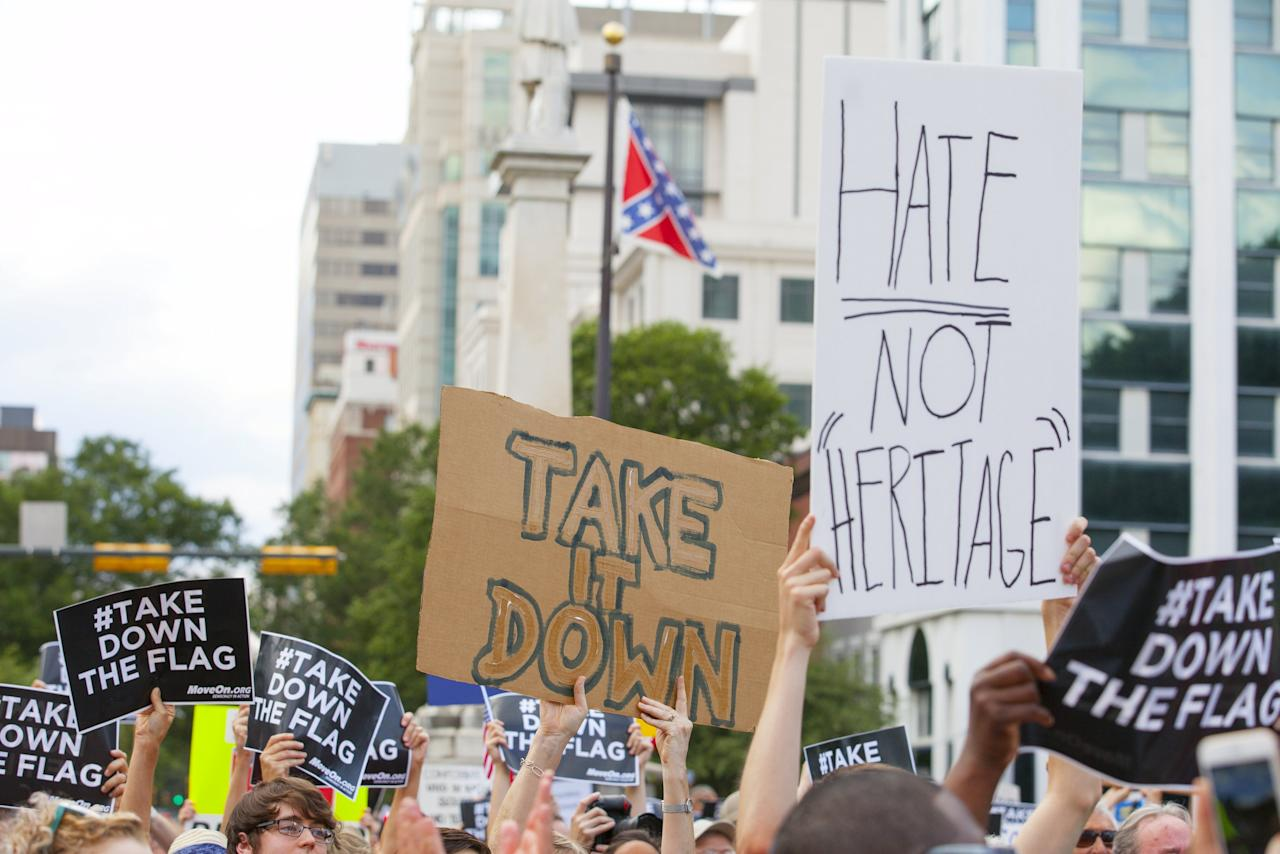 People hold signs during a protest asking for the removal of the confederate battle flag that flies at the South Carolina State House in Columbia, SC June 20, 2015.  REUTERS/Jason Miczek      TPX IMAGES OF THE DAY
