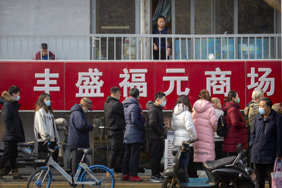 A woman looks at at people lined up for mass COVID-19 testing in a central district of Beijing, Friday, Jan. 22, 2021. Beijing has ordered fresh rounds of coronavirus testing for about 2 million people in the downtown area following new cases in the Chinese capital. (AP Photo/Mark Schiefelbein)
