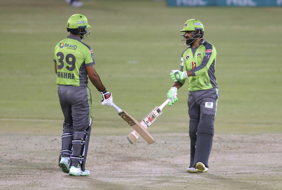 Lahore Qalandars Mohammad Hafeez, right, celebrates with teammate Fakhar Zaman after playing a shot for boundary during a Pakistan Super League T20 cricket match between Lahore Qalandars and Quetta Gladiators at the National Stadium, in Karachi, Pakistan, Monday, Feb. 22, 2021. (AP Photo/Fareed Khan),