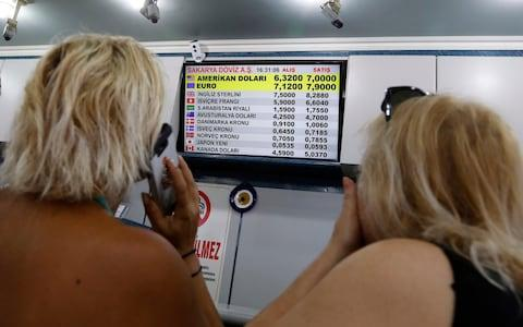 Turkish citizens look at a board showing foreign currency rates inside a currency exchange shop in Ankara, Turkey, Friday, Aug. 10, - Credit: AP