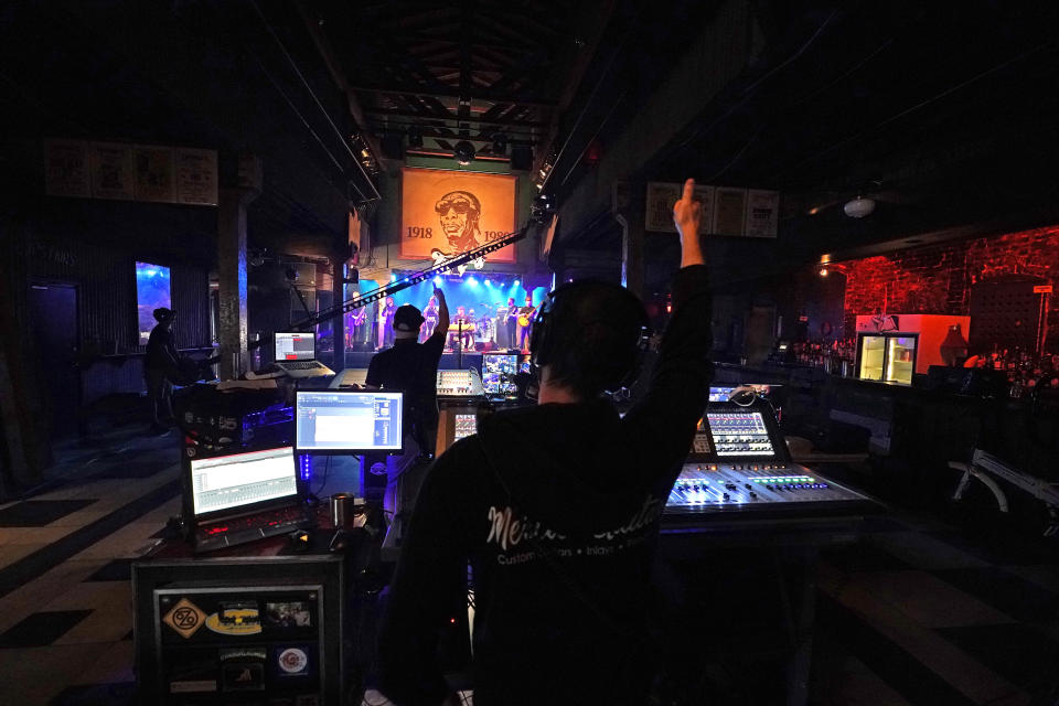 In this Oct. 26, 2020, photo, production engineers give a thumbs up at the end of a song as the band Galactic records a video stream concert, inside an empty Tipitina's music club, which the band owns, in New Orleans. Music clubs all over the nation — pop culture icons like the Troubadour in West Hollywood, the Bluebird Cafe in Nashville, The Bitter End in New York's Greenwich Village — are shuttered due to the coronavirus. And owners fear for the future of their businesses and of a musical way of life. (AP Photo/Gerald Herbert)