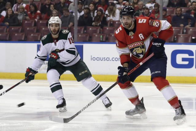 Minnesota Wild center Luke Kunin (19) and Florida Panthers defenseman Aaron Ekblad (5) watch the puck during the first period of an NHL hockey game, Tuesday, Dec. 3, 2019, in Sunrise, Fla. (AP Photo/Lynne Sladky)