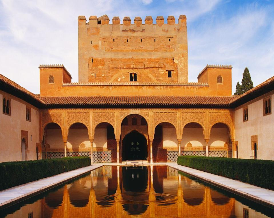 <p>Set in the rolling hills of Granada, this 14th-century fortified palace demonstrates the mastery of Moorish design and architecture. Its origins are clouded in mystery, as it is thought by historians that the current structure may have been built from ancient Roman ruins, though the Alhambra's design as we know it today dates back to the mid 13th century when Nasrid emir Mohammed ben Al-Ahmar began building the sprawling complex.</p><p> After the 1492 Reconquista (Christian reconquest), Alhambra's original mosque was replaced by a church while wings of the palaces were renovated in the Renaissance style. Filled with bountiful gardens, peaceful courtyards, and intricate carvings in Arabic still on the palace walls, the Alhambra stands as a lesson on Granada's fascinating history. </p>