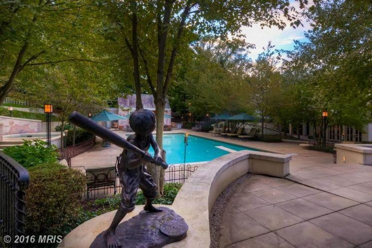 Cal Ripken's pool, with a pool house, torches, deck furniture, and a statue of a boy playing baseball. (Zillow)