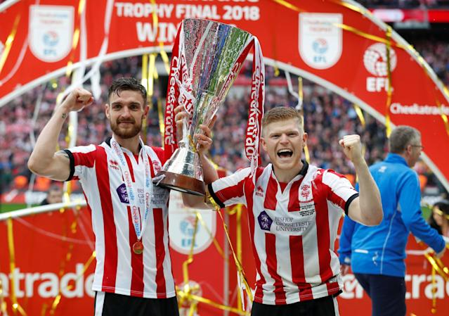 "Soccer Football - Checkatrade Trophy Final - Lincoln City vs Shrewsbury Town - Wembley Stadium, London, Britain - April 8, 2018 Lincoln CityÕs Luke Waterfall (L) and Elliot Whitehouse celebrate with the trophy after winning the Checkatrade Trophy Final Action Images/Matthew Childs EDITORIAL USE ONLY. No use with unauthorized audio, video, data, fixture lists, club/league logos or ""live"" services. Online in-match use limited to 75 images, no video emulation. No use in betting, games or single club/league/player publications. Please contact your account representative for further details."