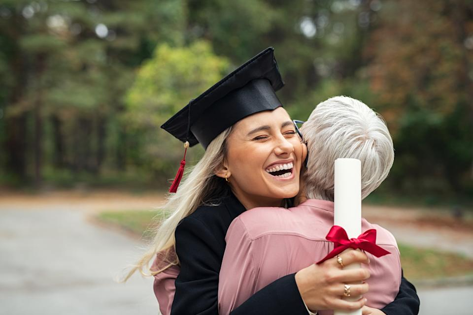 Enthusiastic graduated daughter holding degree embracing mother in campus. Young female student graduate hugging her mother at graduation ceremony. Excited college student with the graduation gown and hat holding diploma and hug the parent at campus.