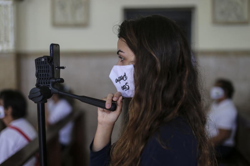 NITEROI, BRAZIL - JUNE 25: A faithful wearing a protective face mask live streams a mass in the Chapel of Sao Pedro during the celebration of Saint Peter day at the Jurujuba fishermen colony amidst the coronavirus (COVID-19) pandemic on June 25, 2020 in Niteroi, Brazil. (Photo by Luis Alvarenga/Getty Images)