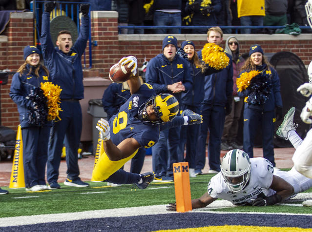 Michigan wide receiver Donovan Peoples-Jones (9) scores a touchdown ahead of Michigan State linebacker Antjuan Simmons (34) during the third quarter of an NCAA college football game in Ann Arbor, Mich., Saturday, Nov. 16, 2019. Michigan won 44-10. (AP Photo/Tony Ding)