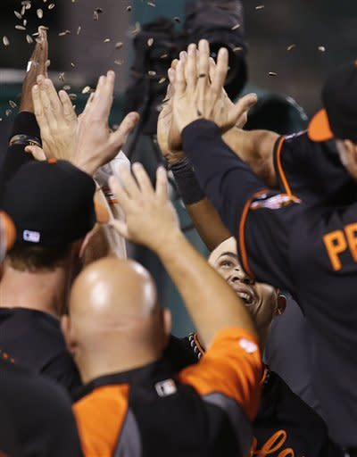 Baltimore Orioles' Steve Pearce, center, is congratulated by teammates after hitting a three-run home run against the Los Angeles Angels in the fifth inning of a baseball game in Anaheim, Calif., Friday, July 6, 2012. (AP Photo/Jae C. Hong)