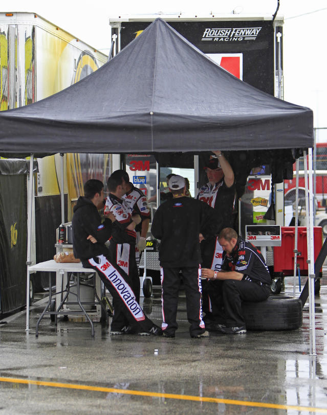 Members of driver Greg Biffle's team waits out a weather postponement in the NASCAR Daytona 500 Sprint Cup series auto race in Daytona Beach, Fla., Monday, Feb. 27, 2012. (AP Photo/John Raoux)