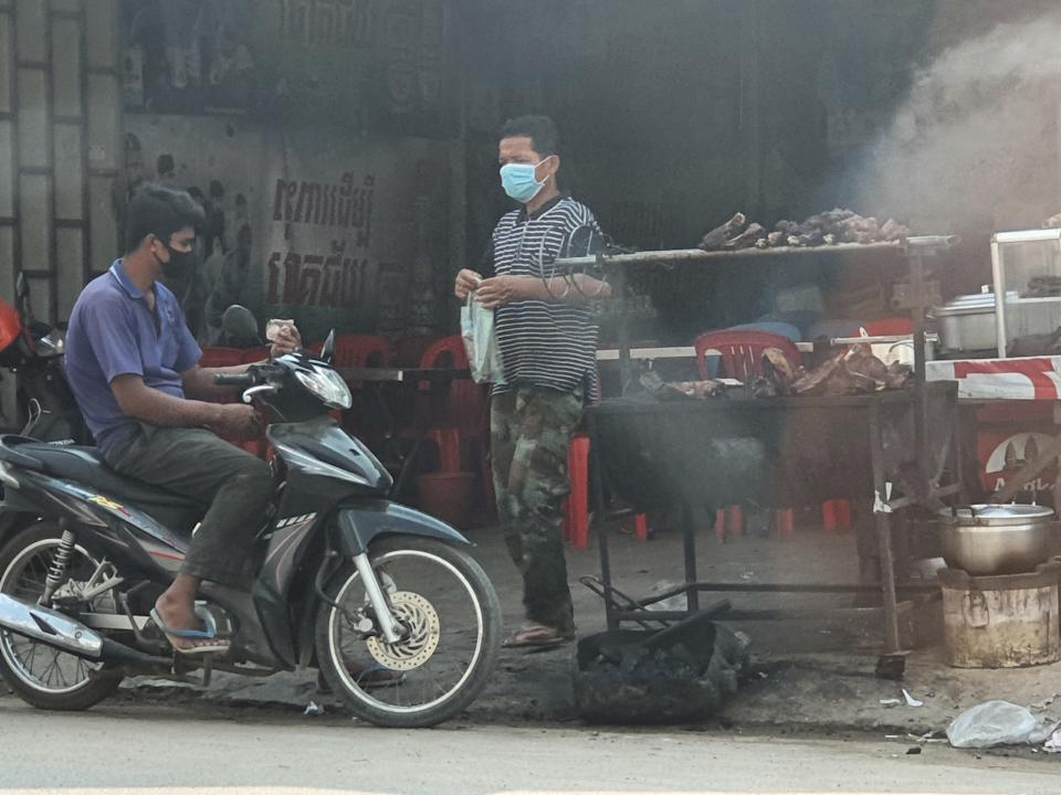 A man in a mask hands a man on a motorbike a bag. Cooking dog parts can be seen in the background.