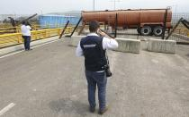 An immigration official observes a fuel tanker, cargo trailers and makeshift fencing, used as barricades by Venezuelan authorities attempting to block humanitarian aid entering from Colombia on the Tienditas International Bridge that links the two countries as seen from the outskirts of Cucuta, Colombia, Wednesday, Feb. 6, 2019. Immigration authorities say the Venezuelan National Guard built the roadblock a day earlier. (AP Photo/Fernando Vergara)