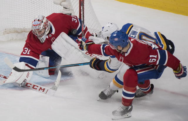Montreal Canadiens goaltender Carey Price makes a save against St. Louis Blues' Brayden Schenn (10) as Canadiens' Xavier Ouellet defends during the third period of an NHL hockey match, in Montreal, Wednesday, Oct. 17, 2018. (Graham Hughes/The Canadian Press via AP)