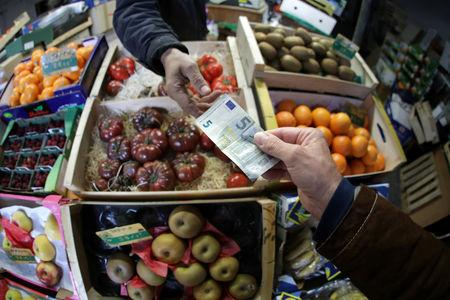 A shopper pays with a Euro bank note in a market in Nice