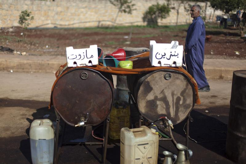 FILE - In this Wednesday, Nov. 7, 2012 file photo, a Syrian man walks behind two containers full of diesel, left, and gasoline, right, for sale on the side of a street in the Syrian village of Atmeh, near the Turkish border with Syria. Syrians face extended blackouts amid severe fuel shortages in the middle of winter and now spend hours in line every day for a few loaves of bread or gasoline at soaring prices, highlighting the mounting difficulty President Bashar Assad faces in providing basic services to his people. (AP Photo/Khalil Hamra, File)
