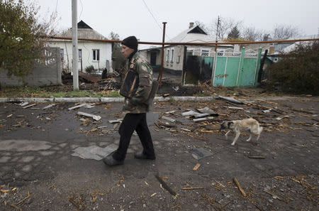 Vladimir Shramko, 48, walks past his neighbor's house, which was damaged by shelling in the village of Spartak, on the outskirts of Donetsk, eastern Ukraine, October 21, 2014. REUTERS/Shamil Zhumatov