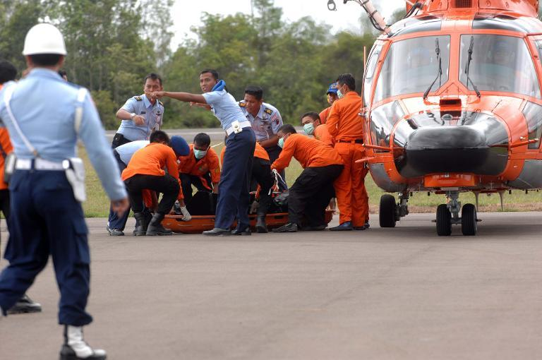 Members of an Indonesian search and rescue team prepare to carry a dead body during the recovery of victims who were onboard the crashed AirAsia flight QZ8501 in Pangkalan Bun on December 31, 2014