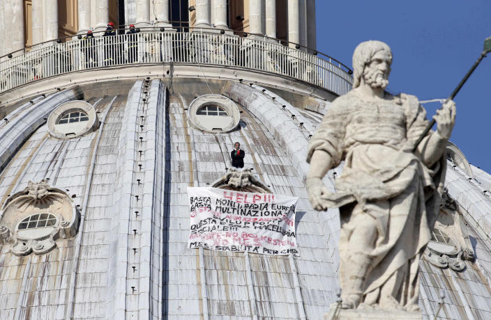 """Firefighters look at Italian businessman Marcello di Finizio standing above his banner which reads in Italian """"Help!! Enough Monti (Italian Premier Mario Monti), enough Europe, enough multinationals, you are killing all of us. Development?? This is a social butchery!!"""", as he protests on St. Peter's 130-meter-high (42-feet-high) dome, at the Vatican, Wednesday, Oct. 3, 2012. An Italian man has eluded Vatican security and scaled the 130-meter-high (42-feet-high) dome of St. Peter's Basilica to protest Italian government and European Union policies. Officials said Wednesday that the man, who identified himself as the owner of a beach resort, refused appeals from government ministers offering to meet with him if he would come down. (AP Photo/Andrew Medichini)"""