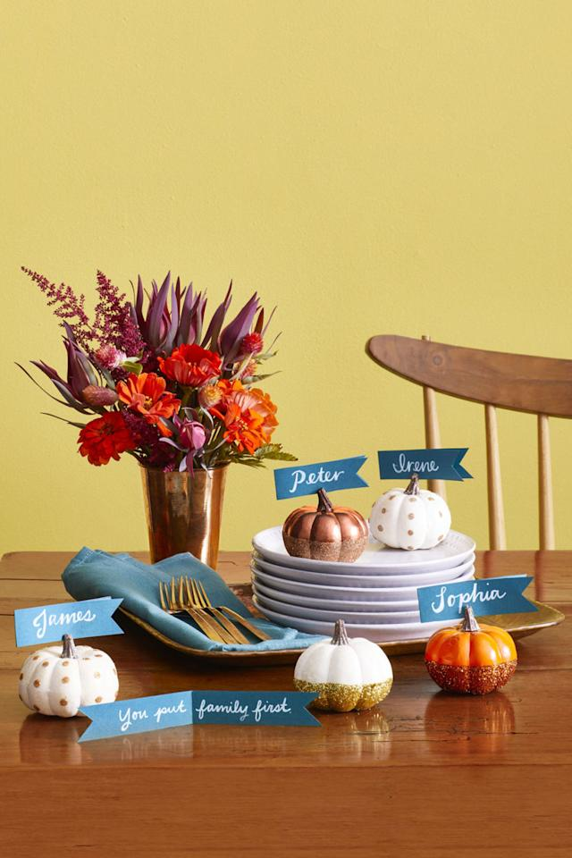 """<p>Tell your loved ones how thankful you are for them with a hidden note inside their Thanksgiving dinner placecard.</p><p>Use a craft knife to cut a triangle in the end of a paper strip, then make a slit in the stem and slide it in.<span> For the polka-dotted pattern, place small glue dots around the pumpkin and sprinkle with fine glitter. For the double-dipped pattern, apply spray paint to the pumpkin, then brush the bottom half with graft glue and gently press into a bowl of glitter. </span></p><p><strong>What you'll need: </strong><span><em><em><em><em>Artificial pumpkins ($17 for 16-pack; <a rel=""""nofollow"""" href=""""https://www.amazon.com/Factory-Direct-Craft-Artificial-Pumpkins/dp/B00FF8Y9HW/?tag=syndication-20"""">amazon.com</a>)</em></em></em><span></span>; Spray paint ($8; <a rel=""""nofollow"""" href=""""https://www.amazon.com/Krylon-Colormaster-Crystal-Clear-Acrylic/dp/B0009X8LZ4?tag=syndication-20"""">amazon.com</a>); Gold glitter ($5; <a rel=""""nofollow"""" href=""""http://www.michaels.com/signature-extra-fine-glitter-recollections-1.5oz/10185451.html"""">michaels.com</a>)</em></span></p>"""
